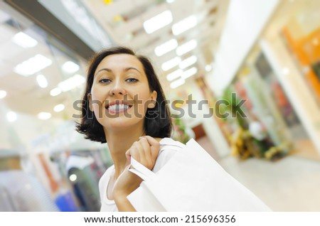 Beautiful shopping woman holding bag and smiling - stock photo