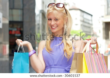 Beautiful shopping woman with bags in city environment.