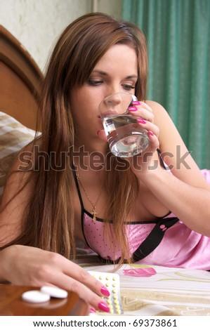 Beautiful sick girl drinks medicine - stock photo