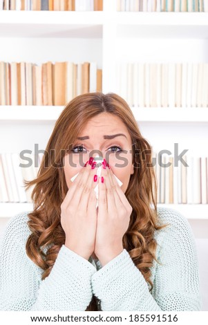 beautiful sick woman with cold and virus sneezing into tissue - stock photo