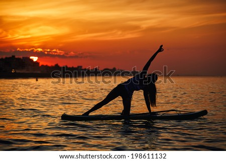 Beautiful silhouette of a slim woman engage paddle board yoga at the perfect orange sunset over the ocean - stock photo