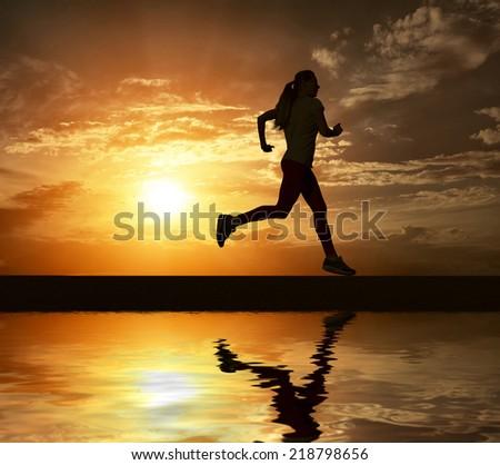 Beautiful silhouette of female running on road under sky with sun light and reflection in water