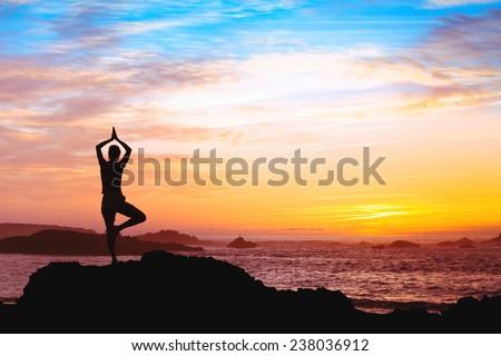beautiful silhouette of woman practicing yoga near the sea - stock photo