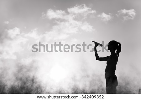 Beautiful silhouette of young woman throwing paper airplane. - stock photo