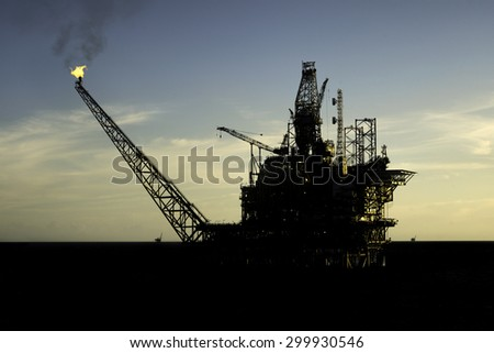 Beautiful silhouette view of an oil processing platform during drilling operation at sea - stock photo