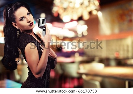 Beautiful singer against abstract background - stock photo