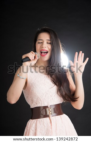 beautiful singer on a black background with a microphone