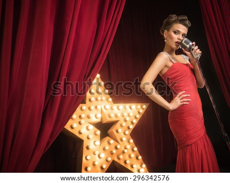 Beautiful singer on the scene - stock photo