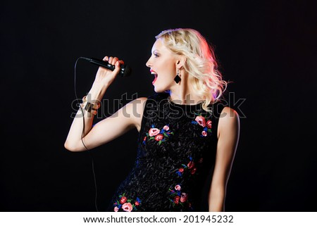 Beautiful singing woman with microphone. Singer. Karaoke song - stock photo