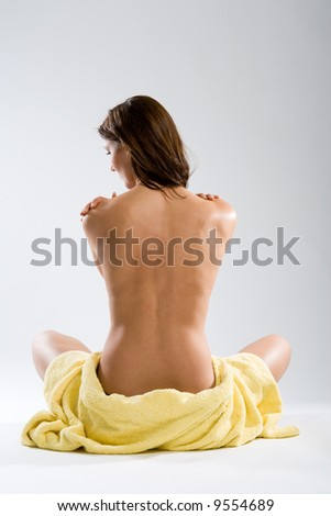 Beautiful sitting naked woman from rear view with towel around hips on white background. - stock photo