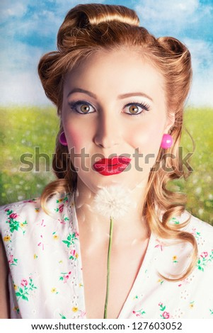 Beautiful Sixties Retro Blonde Woman Wearing Vivid Red Lipstick With Her Hair Rolled Up, Blowing Dandelion Seeds While Making A Wish For New Beginnings - stock photo