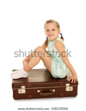 Beautiful , skinny small blonde girl with thin pigtails on the head, in a short summer dress with short sleeves . Girl sitting on a Big old suitcase - Isolated on white background - stock photo