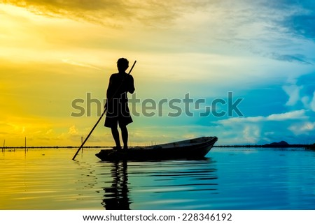 Beautiful sky and Silhouettes of fisherman at the lake, Thailand. - stock photo