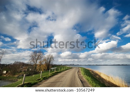 """beautiful sky on a country road in the netherlands with a lake called the """"ijsselmeer"""" to the left - stock photo"""