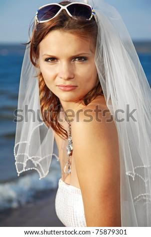 beautiful slavonic bride posing in sunglasses. sea on background. - stock photo