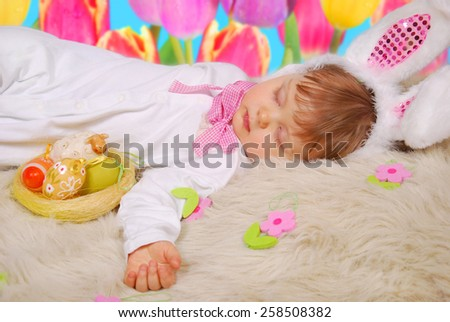 beautiful sleeping baby girl in easter bunny costume with eggs in  basket - stock photo