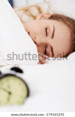 Beautiful sleeping woman with alarm clock. Focus on woman. - stock photo