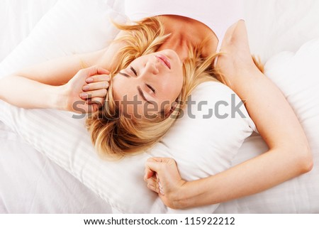 Beautiful sleepy young woman stretching her arms as she lies in bed trying to wake up - stock photo