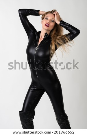 Beautiful slender blonde in a black latex catsuit