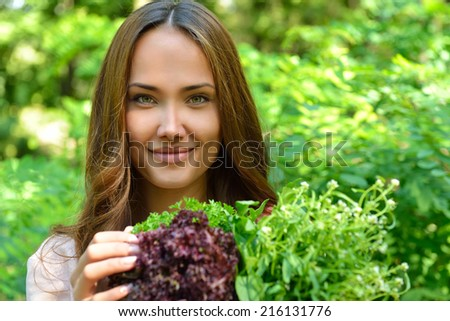 Beautiful slender girl holding healthy fresh greens.  - stock photo