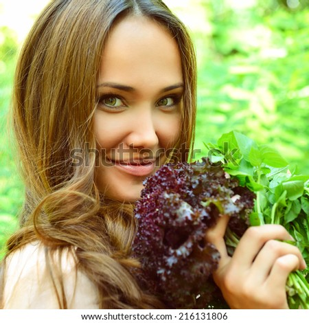 Beautiful slender girl holding healthy fresh greens, toned - stock photo