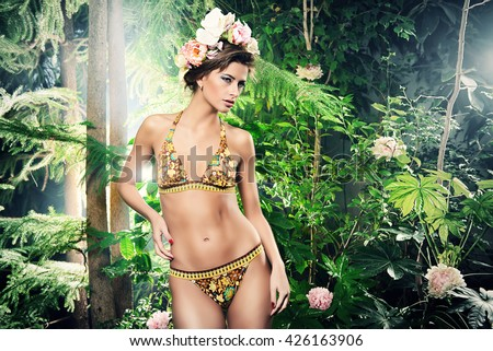 Beautiful slender woman in bikini among tropical plants. Beauty, fashion. Spa, healthcare. Tropical vacation. - stock photo