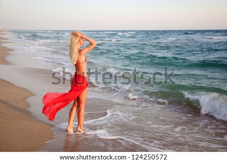 beautiful slender young blonde woman in red skirt and bikini on the sea beach - romantic waiting concept - stock photo