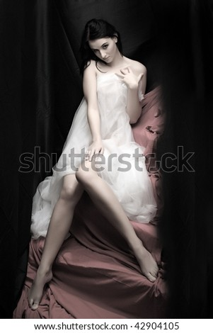Beautiful slenderness young woman in bridal veil on pink background. Low key studio shot. Great for calendar. - stock photo