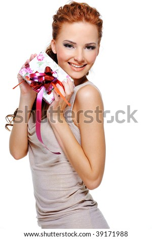Beautiful slim adult girl holding in hands a little white present box with a red ribbon - stock photo