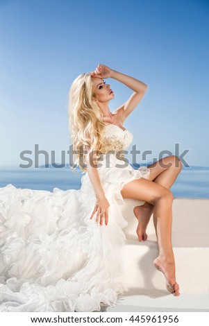 beautiful slim blond girl woman top model bride with long hair and legs in the white bridal ball gown with a long train and flounces stands on a picturesque island of Santorini in Greece - stock photo