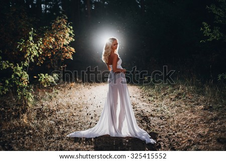 beautiful slim blonde in black long dress in the forest - stock photo
