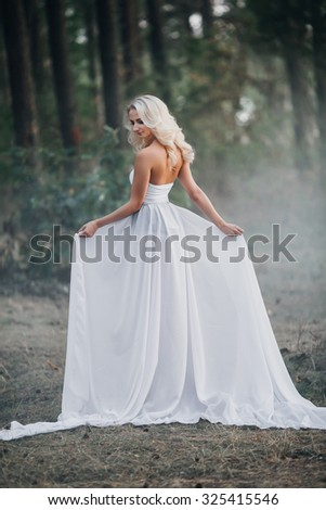 beautiful slim blonde in white dress in the forest - stock photo