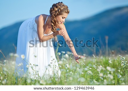Beautiful slim bride in a luxurious wedding dress with flowers. Fashion romantic happy woman. - stock photo