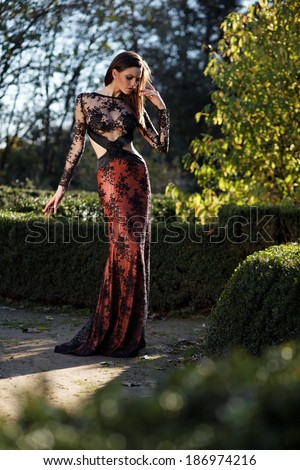 Beautiful slim bride in luxury dress in park on sunset. Romantic girl with glossy hair. Focus on a dress.  - stock photo