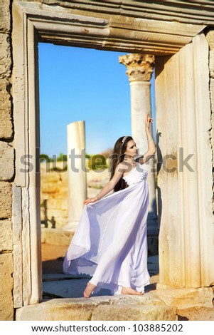 beautiful slim bride in luxury dress on sunset near ancient ruins in wedding day. young woman in Greek  goddess style with diamond tiara and jewelery. Fashion stylish romantic girl with glossy hair. - stock photo