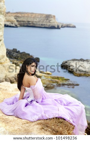 beautiful slim bride posing showing her luxurious wedding silk dress on sunset beach. Fashion romantic stylish arabian young girl with long glossy healthy hair. Spring - summer - stock photo