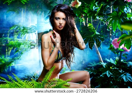 Beautiful slim girl sitting by the pond in the rainforest. Beauty, fashion. Spa, healthcare. Tropical vacation. - stock photo