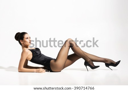 Beautiful, slim lady wearing provocative pantyhose over white background. - stock photo