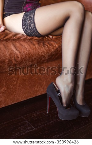 Beautiful slim legs of young woman in black lace stockings and high heels shoes sitting on brown sofa