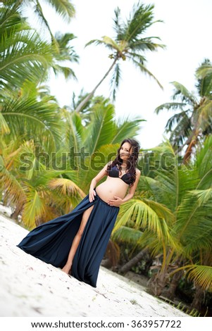 Beautiful slim pregnant girl goes to sandy beach. Tropical nature, palm trees. New life concept - stock photo