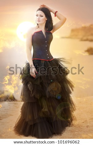 beautiful slim rich woman in luxurious dress on sunset beach. Fashion romantic stylish arabian young girl with long glossy healthy hair. Gothic bride Spring - summer