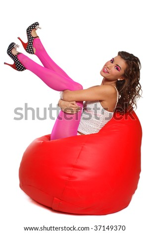 Beautiful slim sexy girl in pink pantyhose and stilettos sitting in red bean bag, over white background - stock photo