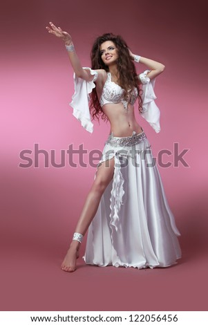 Beautiful slim woman belly dancer. Sexy Arabian oriental professional artist in carnival shining costume with long curly hair. Exotic star of belly dance. Dancing girl brunette - stock photo