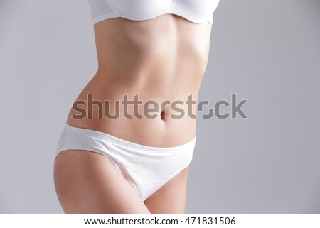 Beautiful slim woman body and sexy belly isolated on gray background