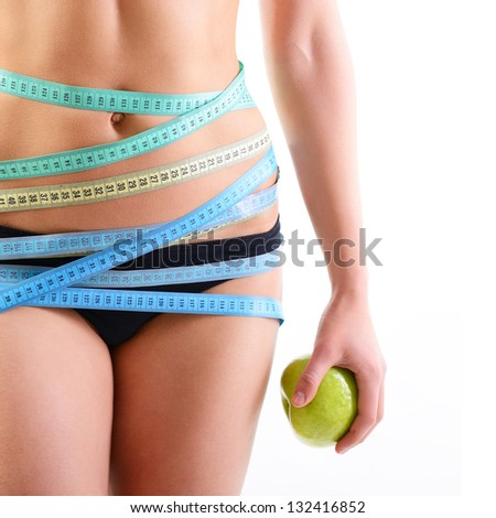 Beautiful slim woman holding green apple and with several color measuring tapes on her waist, over white - stock photo