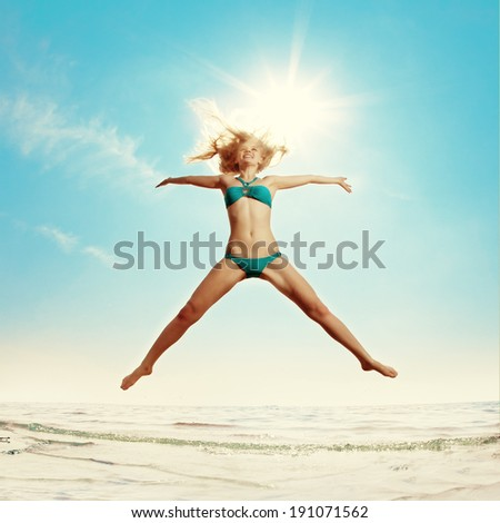 Beautiful slim woman on the beach by the sea. Luxury young girl on the beach near the water. - stock photo