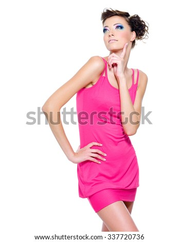 Beautiful slim woman posing in pink dress isolated on white