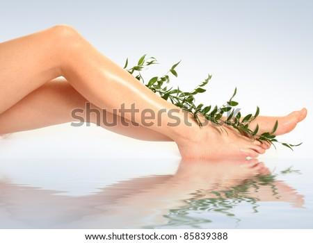 beautiful slim woman's legs on blue - stock photo