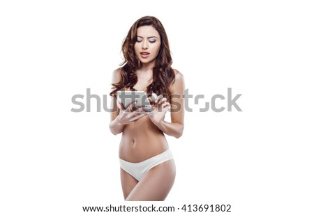 Beautiful slim woman wearing white lingerie. Studio shot of young seductive woman isolated on white background. Woman using tablet computer - stock photo