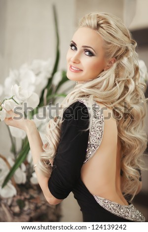 Beautiful slim woman with orchids in black dress in diamond jewelry with hairstyle and bright makeup. Sexy blond girl in fashion dress with flowers at hotel hall. Alluring model posing. tonality.